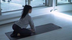 Mujer joven que hace yoga en la estera en el gimnasio con las ventanas del suelo al techo grandes Señora atlética que estira los  almacen de metraje de vídeo