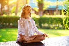 Mujer joven que hace yoga en la naturaleza en parque imagen de archivo