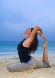Mujer joven que hace yoga en la playa Imagen de archivo libre de regalías