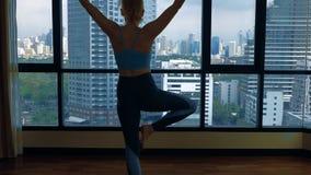 Mujer joven que hace yoga en un cuarto cerca de una ventana grande que pasa por alto los rascacielos almacen de video
