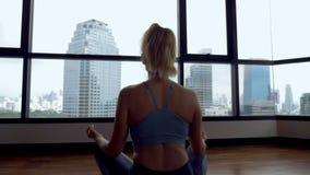 Mujer joven que hace yoga en un cuarto cerca de una ventana grande que pasa por alto los rascacielos almacen de metraje de vídeo