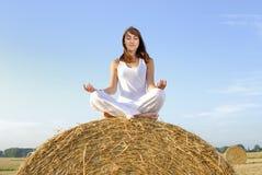 Mujer joven que hace yoga en una bala de la paja Foto de archivo libre de regalías