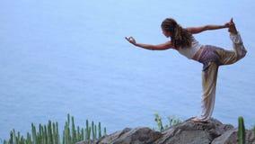 Mujer joven que hace yoga en una costa rocosa en la puesta del sol El concepto de una forma de vida sana armonía Ser humano y nat almacen de metraje de vídeo