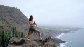 Mujer joven que hace yoga en una costa rocosa en la puesta del sol El concepto de una forma de vida sana armonía Ser humano y nat almacen de video