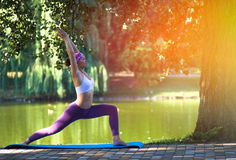 Mujer joven que hace yoga por mañana hermosa cerca del lago Fotografía de archivo libre de regalías