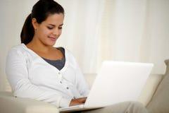 Mujer joven que hojea el Internet en el ordenador portátil Imagen de archivo libre de regalías