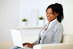 Mujer joven que hojea el Internet en la computadora portátil Foto de archivo libre de regalías
