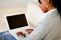 Mujer joven que hojea el Internet en la computadora portátil Imagenes de archivo
