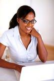 Mujer joven que hojea el Internet en la computadora portátil Fotos de archivo libres de regalías