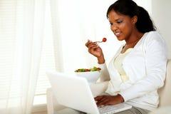 Mujer joven que hojea el Internet que come una ensalada Imágenes de archivo libres de regalías