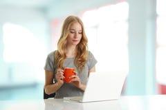 Mujer joven que hojea en el ordenador Foto de archivo libre de regalías