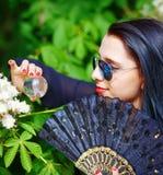 Mujer joven que huele un flor hermoso de Sakura Foto de archivo libre de regalías