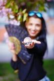 Mujer joven que huele un flor hermoso de Sakura Imágenes de archivo libres de regalías