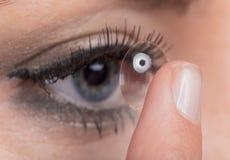 Mujer joven que inserta una lente de contacto imagen de archivo libre de regalías