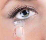 Mujer joven que inserta una lente de contacto fotos de archivo libres de regalías