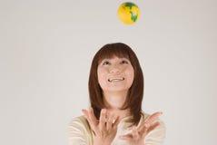 Mujer joven que intenta coger una bola Fotos de archivo libres de regalías