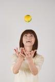 Mujer joven que intenta coger una bola Foto de archivo