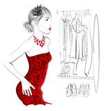 Mujer joven que intenta el vestido rojo Imagen de archivo