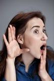 Mujer joven que intenta escuchar algo imagen de archivo libre de regalías