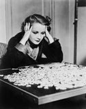 Mujer joven que intenta solucionar un rompecabezas (todas las personas representadas no son vivas más largo y ningún estado exist Imagenes de archivo