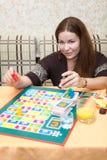 Mujer joven que juega al juego de mesa fotografía de archivo libre de regalías
