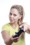 Mujer joven que juega al videojuego con la palanca de mando Fotografía de archivo