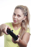 Mujer joven que juega al videojuego con la palanca de mando Imagen de archivo libre de regalías