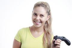 Mujer joven que juega al videojuego con la palanca de mando Foto de archivo libre de regalías