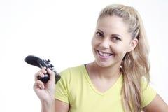 Mujer joven que juega al videojuego con la palanca de mando Foto de archivo