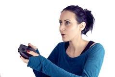 Mujer joven que juega al videojuego en regulador inalámbrico del juego con una expresión facial concentrada imagen de archivo