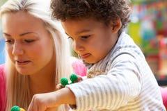 Mujer joven que juega con el muchacho foto de archivo