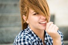 Mujer joven que juega con el pelo Imagenes de archivo
