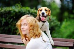 Mujer joven que juega con el perro del beagle en el parque Foto de archivo