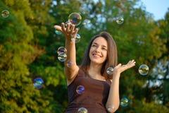 Mujer joven que juega con las burbujas en un parque Fotos de archivo