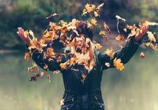 Mujer joven que juega con las hojas de otoño en parque Fotografía de archivo libre de regalías