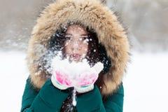 Mujer joven que juega con nieve en parque Imagenes de archivo