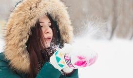 Mujer joven que juega con nieve en parque Foto de archivo libre de regalías