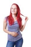 Mujer joven que juega con su pelo Imagen de archivo