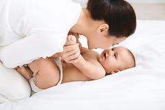 Mujer joven que juega con su pequeño bebé en cama imagenes de archivo