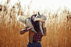 Mujer joven que juega con su perrito del husky siberiano en un campo durante puesta del sol Fotos de archivo libres de regalías