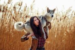 Mujer joven que juega con su perrito del husky siberiano en un campo durante puesta del sol Imagenes de archivo