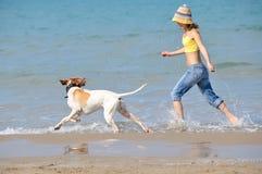 Mujer joven que juega con su perro Foto de archivo