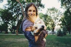 Mujer joven que juega con su perro en el parque imagenes de archivo