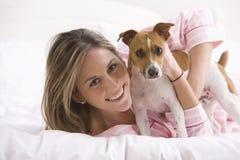 Mujer joven que juega con su perro en la cama Imagen de archivo libre de regalías