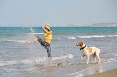Mujer joven que juega con su perro en la playa Imagen de archivo