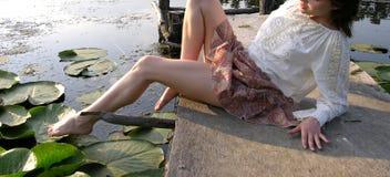 Mujer joven que juega con sus piernas? Imagen de archivo
