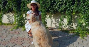 Mujer joven que juega con un perro almacen de metraje de vídeo