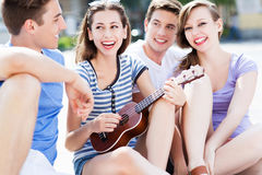 Mujer joven que juega el ukelele para los amigos Fotografía de archivo