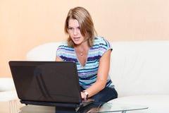 Mujer joven que juega en juegos en la computadora portátil Imagen de archivo