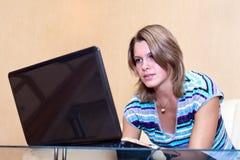 Mujer joven que juega en juegos en la computadora portátil Fotos de archivo